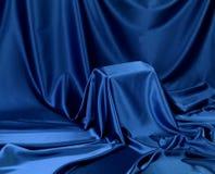 Hidden blue secret. Something secret veiled under satin silky cloth fabric stock image