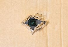 Hidden camera in torn hole in cardboard paper Royalty Free Stock Photography