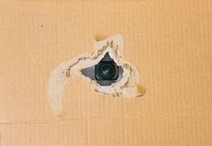 Hidden camera in torn hole in cardboard paper. Hidden camera lens spying through torn hole in cardboard paper Royalty Free Stock Image