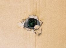 Hidden camera in torn hole in cardboard paper. Hidden camera lens spying through torn hole in cardboard paper Royalty Free Stock Photos