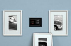 Hidden Closed Wall Safe Behind Picture. A closed hidden wall safe revealed behind a hanging framed picture on a flat blue wall in a house - 3D render stock images
