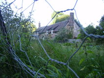 Hidden country cottage. Cottage hidden in the country with wire fence in the front Royalty Free Stock Photography