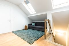 Hidden sofa in attic. Hidden, grey sofa with cushions in the attic next to stairs and colorful rug royalty free stock images