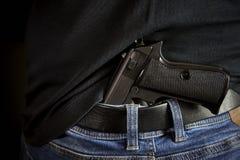 Hidden gun back side to man in blue jeans.