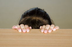 Hidden head of girl. A brown haired girl is hidden behind a table. Only hairs and fingers are visible royalty free stock photos