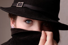 Hidden Identity. Portrait of girl wearing hat. Face partially hidden by collar stock photography