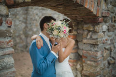 Hidden kiss of bride and groom Royalty Free Stock Photo