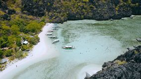 Hidden lagoon of star beach on Tapiutan island near Matinloc shrine. El Nido, Palawan, Philippines. Many boats stops for stock video footage