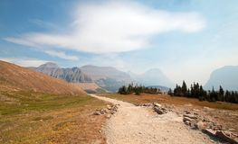HIDDEN LAKE HIKING TRAIL ON LOGAN PASS UNDER CIRRUS CLOUDS DURING THE 2017 FALL FIRES IN GLACIER NATIONAL PARK IN MONTANA USA. HIDDEN LAKE HIKING TRAIL ON LOGAN royalty free stock photography