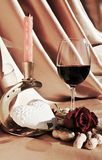 Hidden love. A glass of red wine next to a rose and a candle on a beautiful background, suggesting a hidden love stock photography