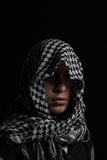 Hidden man with palestinian scarf over head. In front of isolated black background Royalty Free Stock Photography