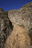 Hidden Mountain Grass. A strip of grass winding its way between a couple of large boulders, hidden atop a mountain Stock Image
