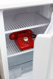 Hidden phone. Hidden vintage British red phone in a fridge Royalty Free Stock Photography