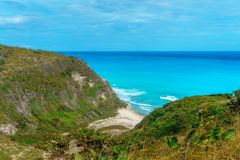 Hidden picturesque Caribbean Bay, azure sea and green cliffs royalty free stock images