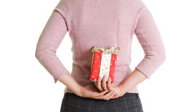 Hidden present. Red Christmas present hidden behind back Royalty Free Stock Photography
