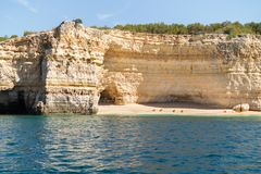 Hidden remote beach covered with limestone walls. Kayak left on the beach by tourists went for cave exploring. Algarve Portugal Royalty Free Stock Photos