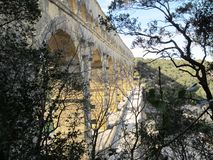 Looking at Pont du Gard, an old Roman aqueduct, from the side behind the trees royalty free stock photography
