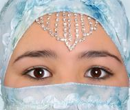Hidden in silk. Beautiful young woman with mysterious eyes, wearing a blue silk veil Stock Photography