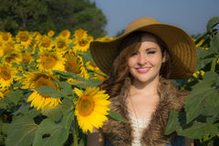 A hidden smile among sunflowers. Acres and acres of sunflowers and one beautiful, smiling brunette Royalty Free Stock Image