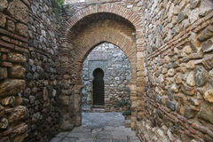 Hidden stone passageway in Malaga fortress with archs and gate Royalty Free Stock Image