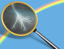 Hidden truth. Clear Sky with Rainbow and Storm seen through Magnifying glass - conceptual for Hidden Truth Royalty Free Stock Photography