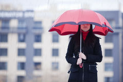 Hidden under umbrella Stock Images