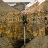 Hidden waterfall high Arctic. A large, powerful waterfall sits between two rugged stone Arctic cliffs stock photo