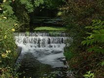 Hidden waterfallwith sun sneaking through the trees royalty free stock photo