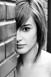 Hidden woman. Woman looking behind a brick wall Stock Photography