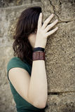 Hidden woman. Hidden young woman behind stone wall Stock Images
