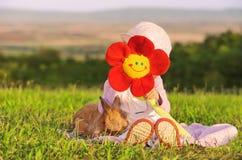 hidding在花后的小女孩和她的兔子 图库摄影