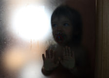Hide. Little hides behind the door glass Royalty Free Stock Photography