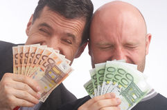 Hide. Two businessmen hiding behind a fan made out of paper-money Royalty Free Stock Image