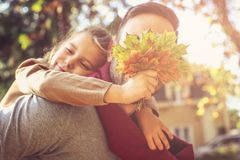 Hide Daddy with leaves. Single father. Hide Daddy with leaves. Single young father with daughter in nature Royalty Free Stock Photo
