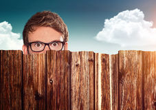 Hide. Man hiding behind a fence Royalty Free Stock Image