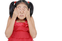 Hide and seek. Girl covering eyes with hands ignoring over white background Stock Photography