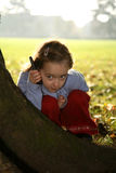 Hide and seek. Young girl playing hide and seek holding a mobile phone Royalty Free Stock Photos