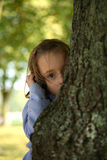 Hide and seek. Young girl playing hide and seek holding a mobile phone Stock Photo
