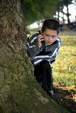 Hide and seek. Young boy playing hide and seek holding a mobile phone Stock Image