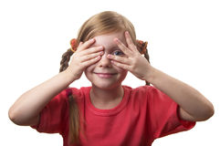 Hide and seek. Little girl peep thru hand with one eye isolated over white background Royalty Free Stock Photo