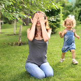 Hide and seek. Woman and child playing hide and seek in summer park stock photos
