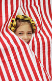 Hide and seek. Laughing young girl with hair curlers peeking through the stripy curtain Stock Photography