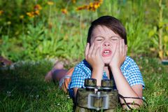 Hide and Seek. The boy squeezes his eyes and counts to 10. The binocular lies in front of the child Royalty Free Stock Photography