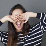 Hide-and-seek concept. Joyous brunette girl hiding her eyes for fun game and surprise herself,grey background Royalty Free Stock Photography