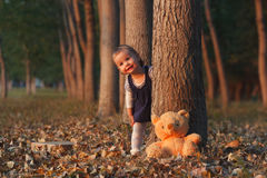 Hide and seek. Cute little girl is playing hide and seek with her Teddy bear Royalty Free Stock Photo