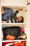 Hide and seek. Funny boy playing hide and seek hiding in a closet stock photos