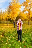 Hide and seek game in the autumn park. Kids play hide and seek with boy counting covering face with palms while others hiding behind autumn male trees Royalty Free Stock Photo