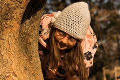 Hide seek and girl. Girl play outdoors in the park on sunny November day. Girl hiding behind a tree Stock Photos