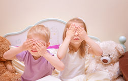 Hide and seek. Little brother and sister play in hide and seek at home, covered eyes with hands, having fun together, family relationship, happy childhood Royalty Free Stock Photography