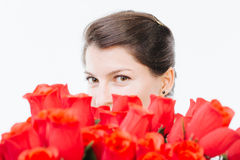 Hide and seek. Mysterious woman hiding behind red roses - isolated on white Stock Photo